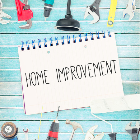 home improvements: The word home improvement against tools and notepad on wooden background Stock Photo