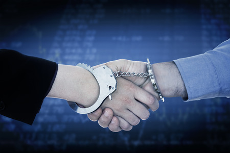 restraining device: Business people in handcuffs shaking hands against stocks and shares