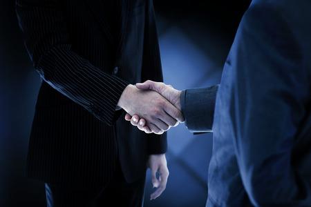 Handshake business: Business people shaking hands against dark grey room