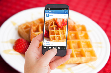 Female hand holding a smartphone against waffles and half cut strawberry together in a white plate