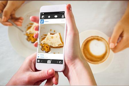 indulgence: Hand holding smartphone against photo sharing app