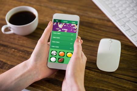 Woman using smartphone against gambling app screen Stock Photo