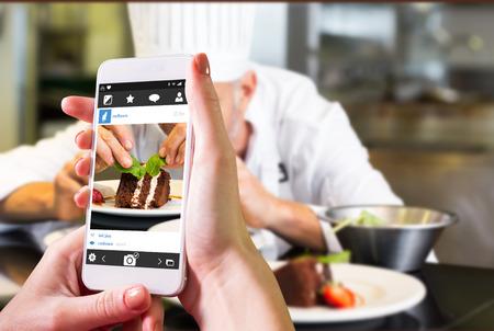 decoracion de pasteles: Mano que sostiene teléfono inteligente contra concentrada masculina postre decoración chef de pastelería en la cocina