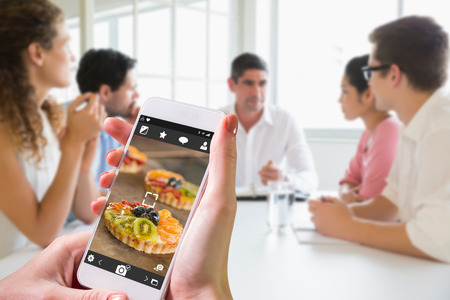 tarts: Hand holding smartphone against tray of sweet pastry tarts