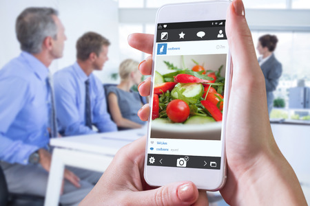 garden staff: Hand holding smartphone against close up of a garden salad