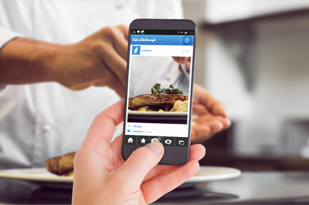 female chef: Female hand holding a smartphone against closeup mid section of a chef putting salt Stock Photo