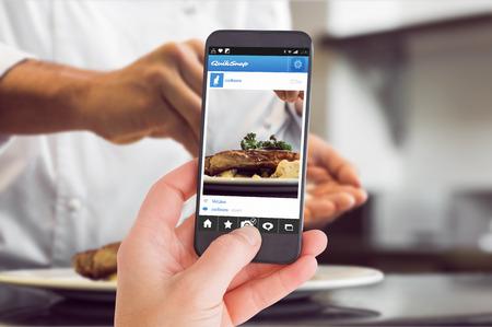 cocinero: Mano femenina que sostiene un teléfono inteligente contra la sección media de cerca de una sal cocinero poniendo