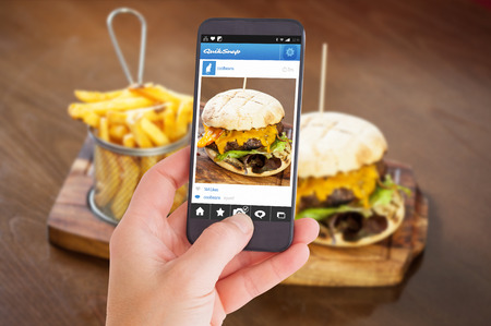 main course: Female hand holding a smartphone against close up on a cheese burger and french fries