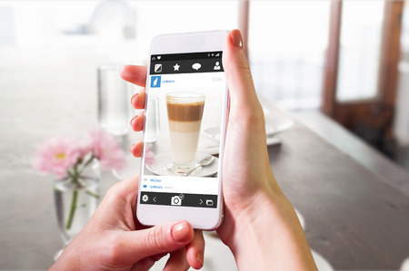 Hand holding smartphone against latte and coffee on table
