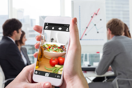 teaming up: Hand holding smartphone against close up of salad