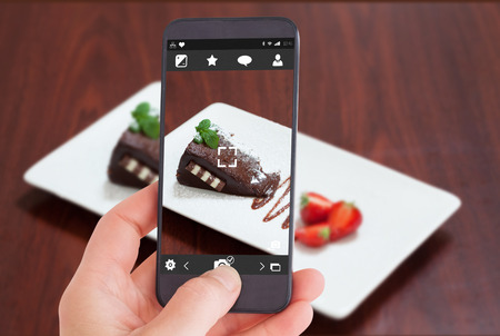 indulgent: Female hand holding a smartphone against front view of chocolate cake with strawberries Stock Photo