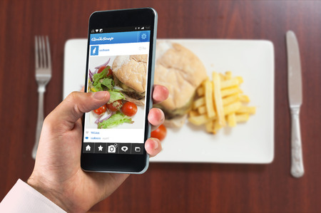 indulgent: hand holding smartphone against overhead view of burger with french fries and salad