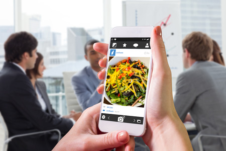 hot stone: Hand holding smartphone against components of cook it yourself fish dish with hot stone Stock Photo