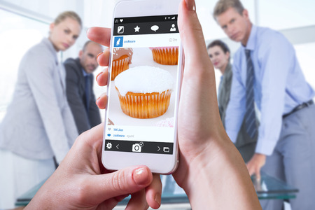 restless: Hand holding smartphone against muffins with icing sugar Stock Photo