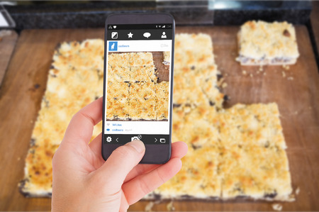 indulgent: Female hand holding a smartphone against close up of piece of pastry with fruit