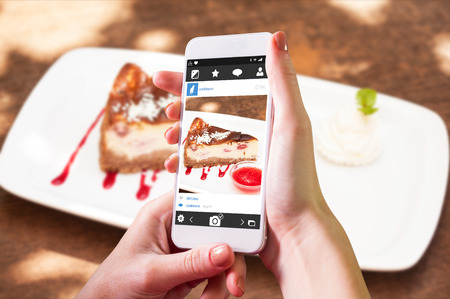 chantilly: Hand holding smartphone against cheesecake with chantilly cream and coulis