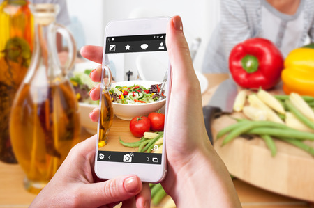 Hand holding smartphone against close up of salad