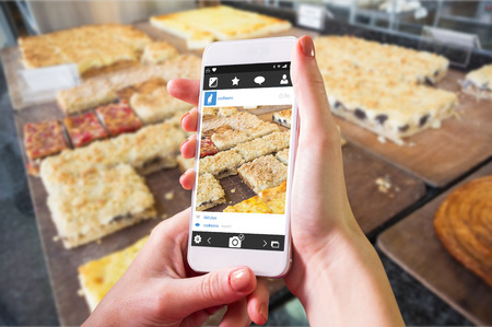 indulgent: Hand holding smartphone against pastry with fruit on counter