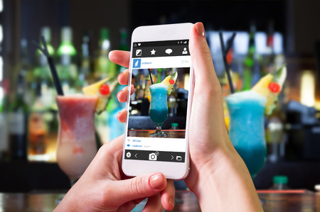 mouth watering: Hand holding smartphone against close up on mouth watering cocktails Stock Photo