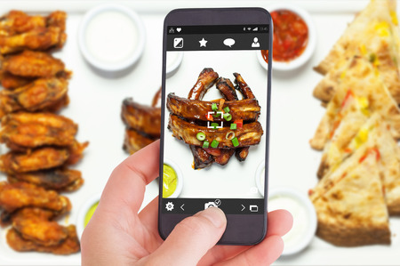 dial plate: Female hand holding a smartphone against overhead of an appetizing platter of finger food