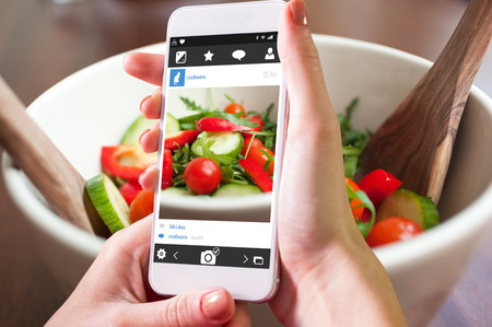 healthy living: Hand holding smartphone against close up of a garden salad