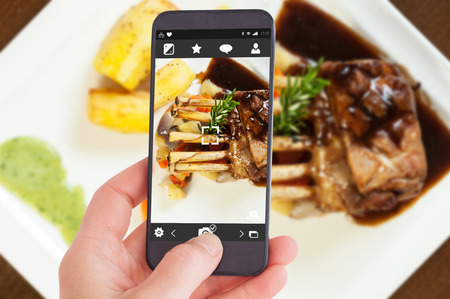 roast lamb: Female hand holding a smartphone against delicious rack of lamb dish with roast vegetable and potatoes Stock Photo