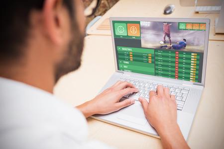Gambling app screen against man using laptop