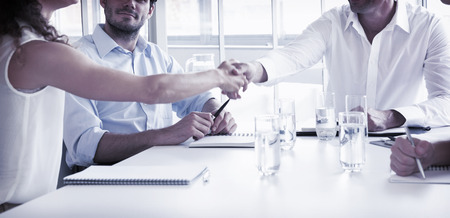 sitting at table: Business partners shaking hands at conference table in office