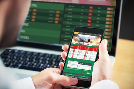 icono deportes: Hombre de negocios usando smartphone frente a la pantalla de aplicaciones de juegos de azar