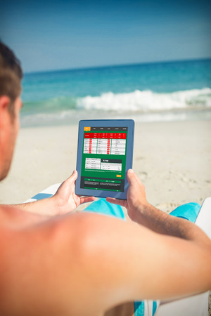 using tablet: Man using digital tablet on deck chair at the beach against gambling app
