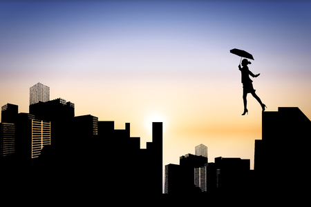 stepping on: Businesswoman stepping with umbrella against cityscape silhouette Stock Photo