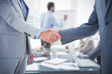 Business handshake against young business people in board room meeting Stock Photo