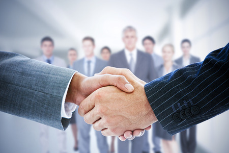 young man smiling: Composite image of business people shaking hands
