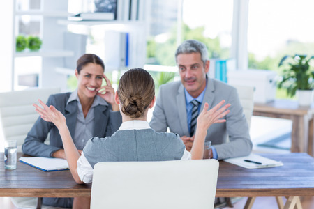interview: Business people interviewing young businesswoman in office