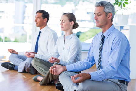 yoga meditation: Business people doing yoga on floor in office Stock Photo