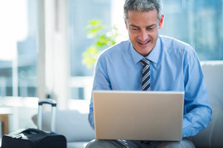 Happy businessman using laptop computer in living room