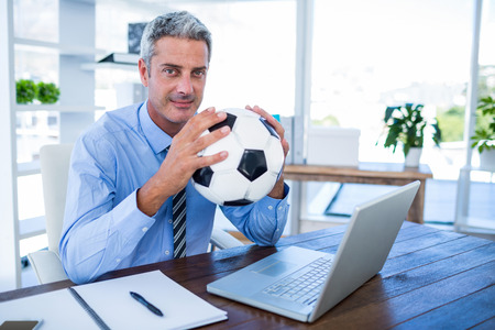 swivel: Happy businessman looking at camera and holding foot ball in office
