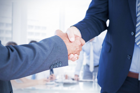 Businessmen shaking hands against business people in office at presentation Stock Photo