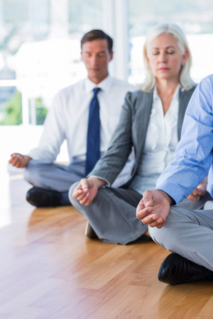 team lotus: Business people doing yoga on floor in office Stock Photo