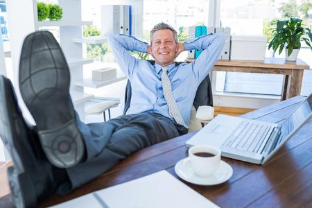 swivel chair: Businessman relaxing in a swivel chair in office