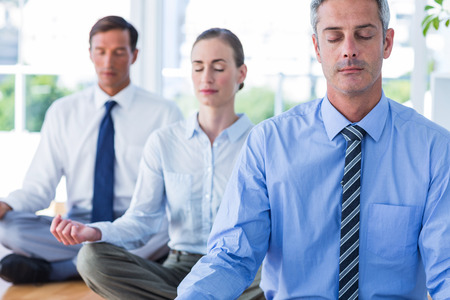 meditating: Business people doing yoga on floor in office Stock Photo