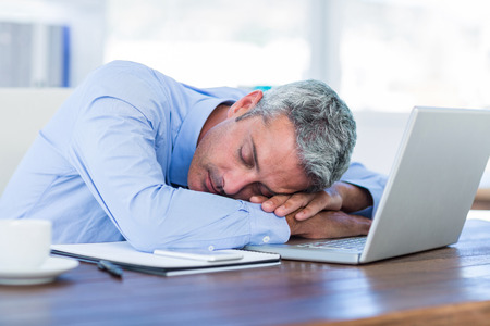 asleep chair: Businessman sleeping on laptop computer in office