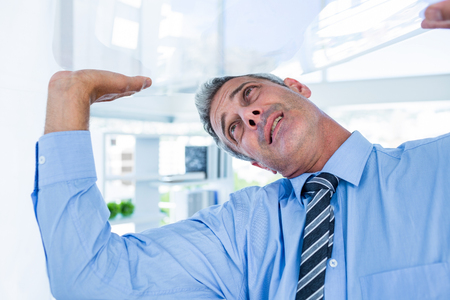 serious businessman: A serious businessman lifting something in office Stock Photo