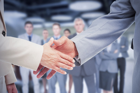 Composite image of close up of business people shaking their hands