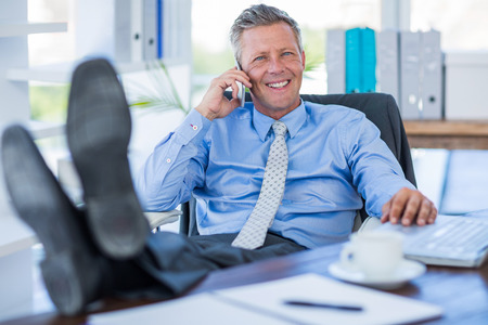 swivel chair: Businessman relaxing in a swivel chair and having a phone call in office