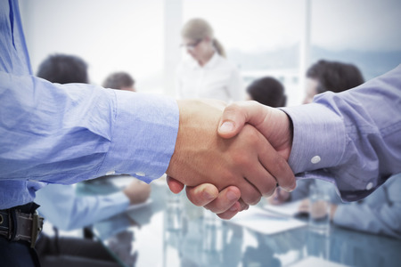 female hand: Two men shaking hands against business people in board room meeting Stock Photo