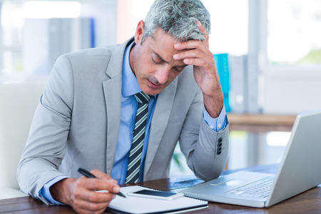 irritated: Irritated businessman trying to work in office Stock Photo