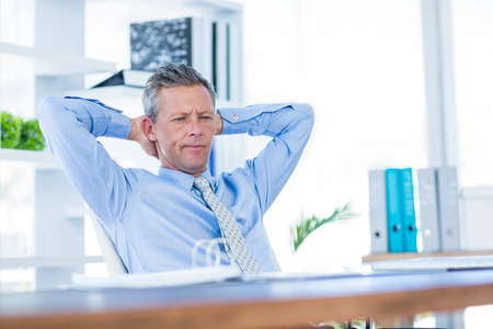 swivel: Thoughtful businessman relaxing in swivel chair in office Stock Photo
