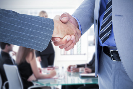 co: Businessman shaking hands with a co worker against businesswoman reporting to sales in a seminar Stock Photo