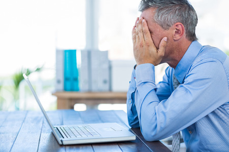 irritated: Irritated businessman with hands on head in office Stock Photo